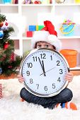 Child with clock in anticipation of New Year