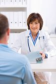 foto of male nurses  - Smiling senior female doctor talking with male patient at office - JPG