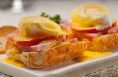 stock photo of benediction  - fresh eggs benedict on bread with tomato and ham - JPG