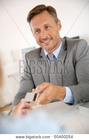 Banker giving credit card to client