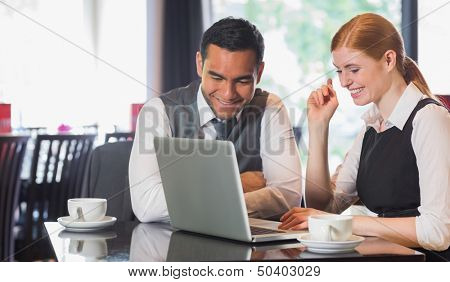 Happy business team working together in a cafe with laptop