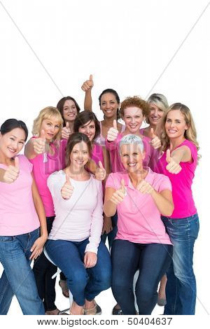 Voluntary cheerful women wearing pink for breast cancer on white background