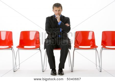 Businessman sitting in Zeile leere Stühle