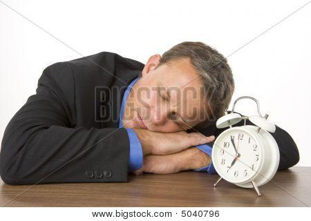Businessman Asleep On Desk By An Alarm Clock
