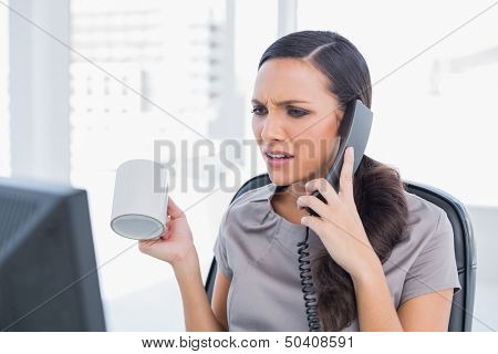 Irritated secretary answering phone in her office and looking at computer screen