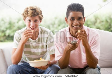 Teenage Boys Sitting On Couch Eating Crisps Together