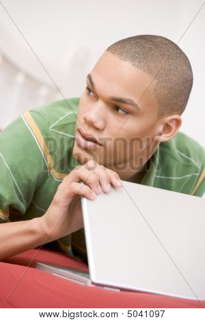 Teenage Boy Lying On Bed Using Laptop