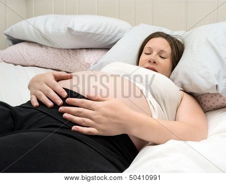 Pregnant Young Woman Lying Down Hands On Stomach Feeling Happy And Confident