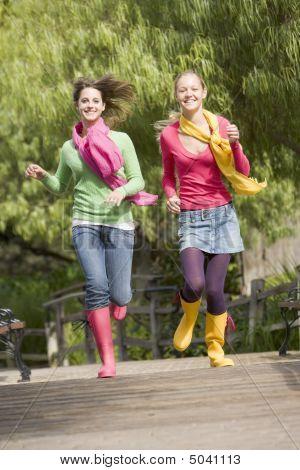 Pair Of Teenage Girls Jogging In Park
