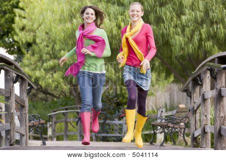 Pair Of Teenage Girls Jogging In Park