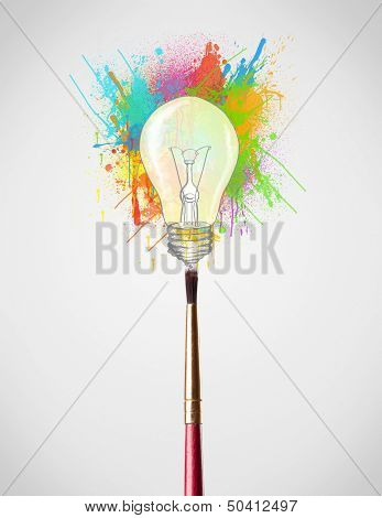 Paintbrush close-up with colored paint splashes and lightbulb concept