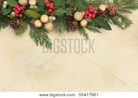 Christmas background border with gold baubles, natural holly, mistletoe, ivy, fir leaf sprigs and pine cones over parchment.