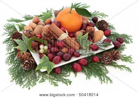 Christmas cranberry and mandarin orange fruit with nuts, spice and winter greenery over white background.