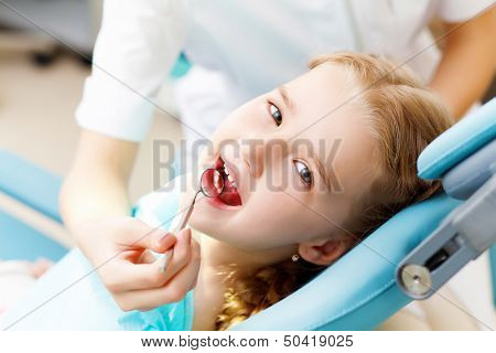 Little girl sitting in the dentists office