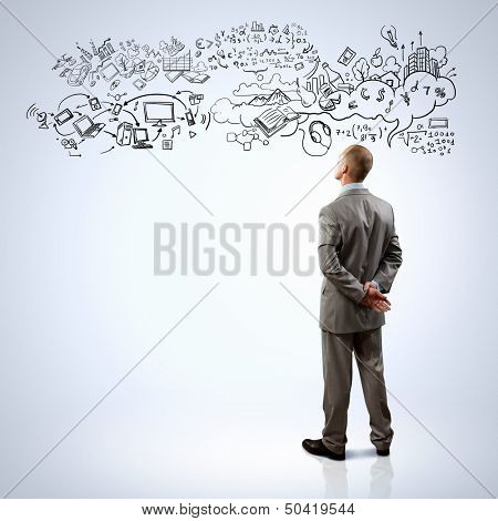 Back view of businessman looking at collage drawing
