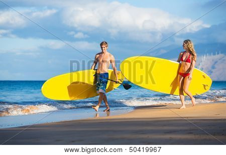 Attractive Couple with Stand Up Paddle Boards, SUP, on the beach in Hawaii