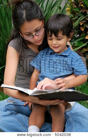 Young Hispanic Mother Reading To Her Child