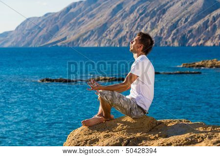 Handsome man in a yoga position on the beach