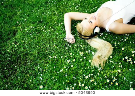 Woman Lying On Grass With Headphones
