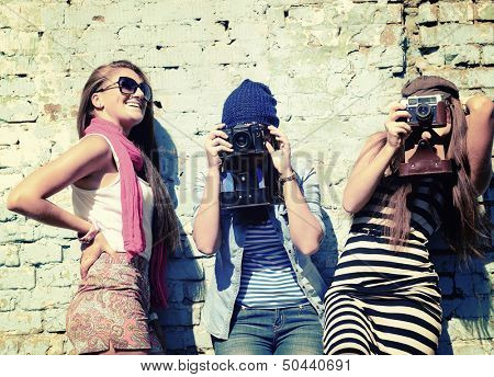 urban girls have fun with vintage photo cameras outdoor near grunge wall, image toned and noise added