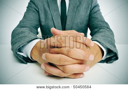 man wearing a suit sitting in a table with clasped hands