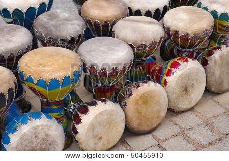 Many colorful congas or hand-drums for sale in a handicraft market