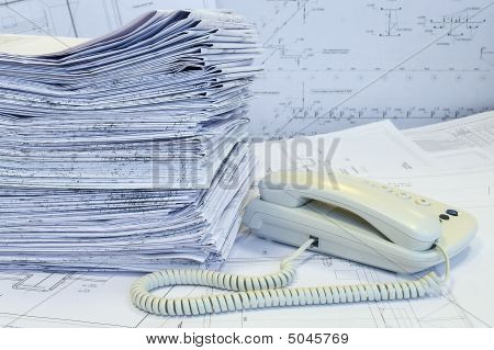 White Phone And Heap Of Formed Project Drawings