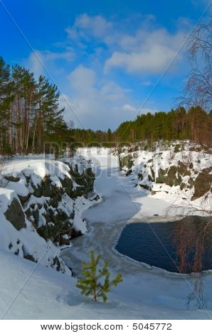 Snowy Riverbed In Middle Of  Forest With Open Basin Of Water
