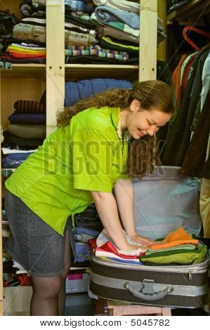 Woman In The Wardrobe Packs Things Into A Suitcase