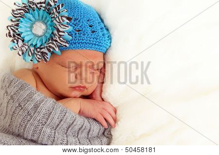 Newborn baby asleep on a purple blanket