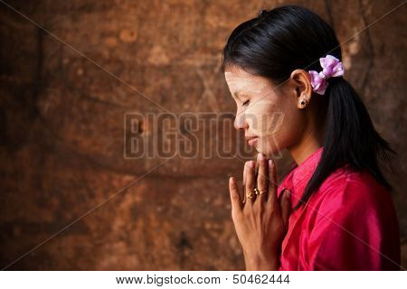 Beautiful traditional Myanmar girl in a praying pose.
