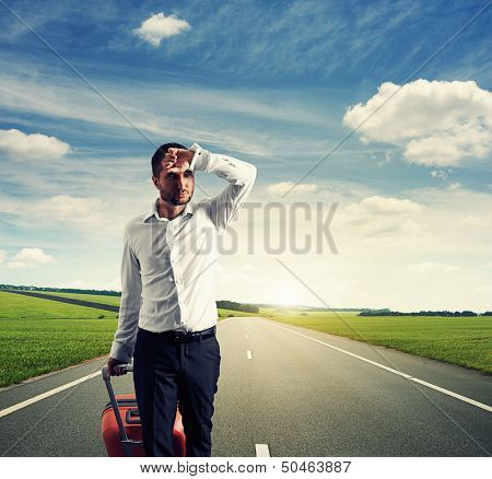 tired young businessman with suitcase walking on the road