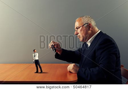 frightened worker under magnifying glass his boss