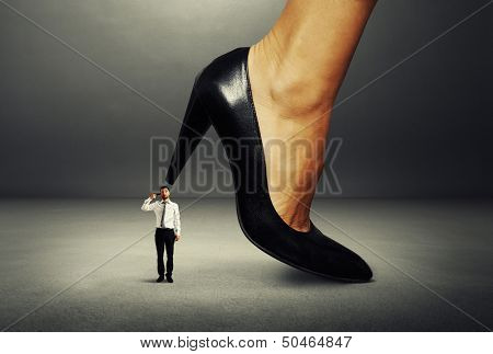 small man with gun under big female heel