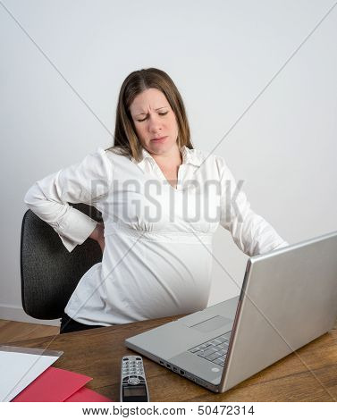 Pregnant Woman Stretching Her Aching Back Sitting At A Desk