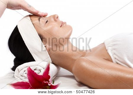 Young woman receiving facial massage, beauty treatment, side view.