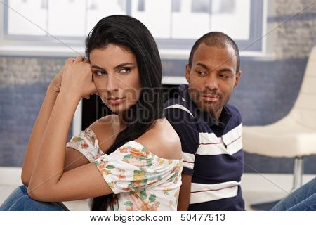 Diverse couple sitting on floor after fighting disappointed and angry.