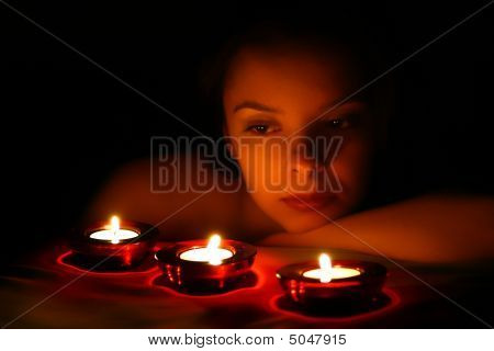 Woman Looking On Three Candles