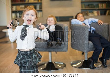 A girl with a magnifying glass shows tongue and two boys sitting on chairs