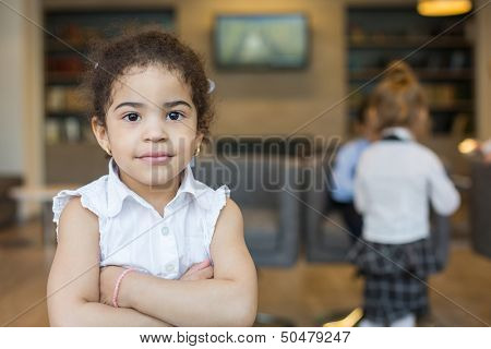 Mulatto girl with a bracelet on his hand in a business center with other children