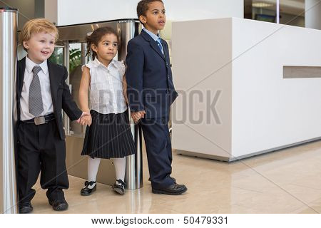Caucasian boy and a mulatto girl with a boy standing holding hands near the turnstiles in the business center