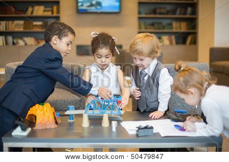 Four little children in business dress playing with toys on the table in the business center, one girl draws a diagram