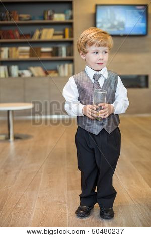 A little boy in a business clothes with empty glass in the business center
