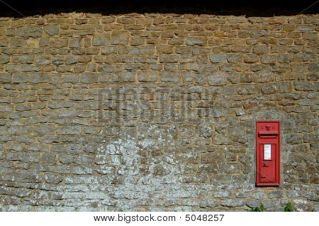 Red English Postbox Isolated In Stone Wall