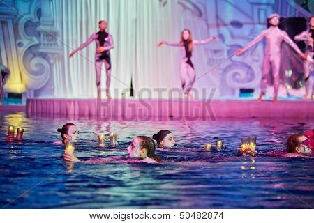 MOSCOW - JAN 8: Swimmers swim with burning candles in their hands in Swimming Pool of Sports complex Olympyisky during musical show Through the Looking Glass, January 8, 2013, Moscow, Russia.