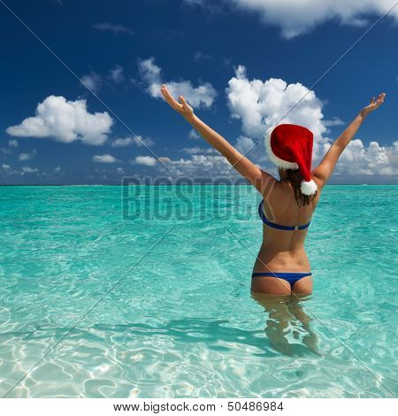 Woman in santa's hat in bikini at tropical beach