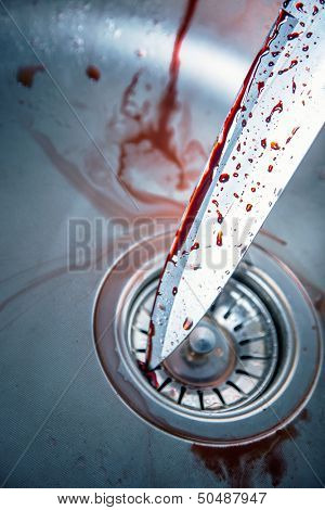Bloody knife in kitchen sink for Halloween or crime