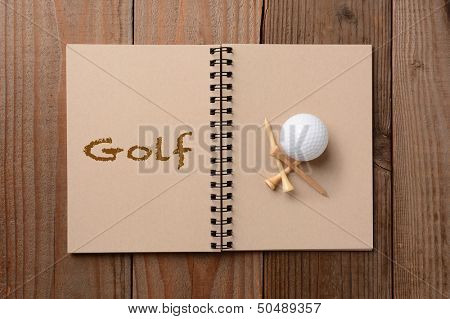 A golf ball and tees on the blank page of a notebook. The opposite page has the word Golf spelled out. Horizontal format on a rustic wooden table.