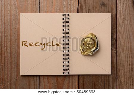 A crushed soda can on the blank page of a notebook. The opposite page has the word Recycle spelled out. Horizontal format on a rustic wooden table.