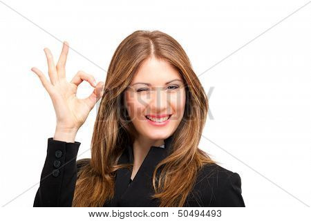 Portrait of beautiful girl showing OK sign and winking. Isolated on white.
